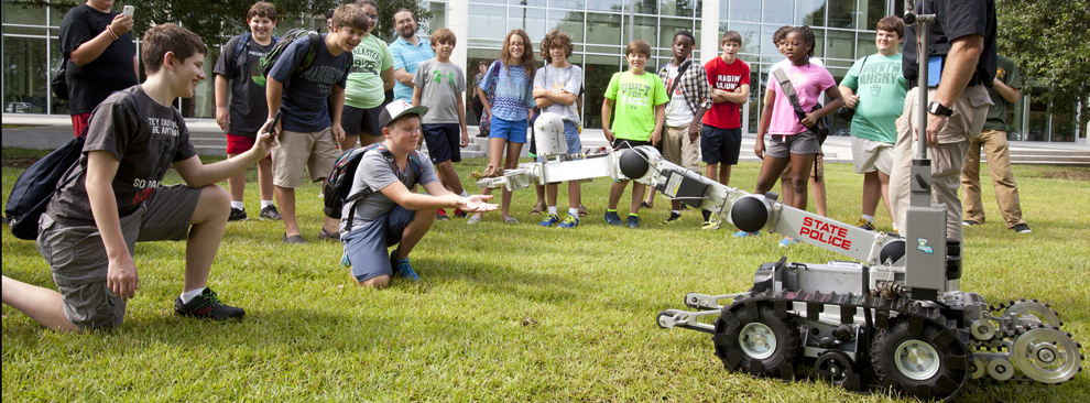 RoboFit camp participant Mason Delahoussaye of Madisonville prepares to catch a rock being carried by a Louisiana State Police bomb squad robot.