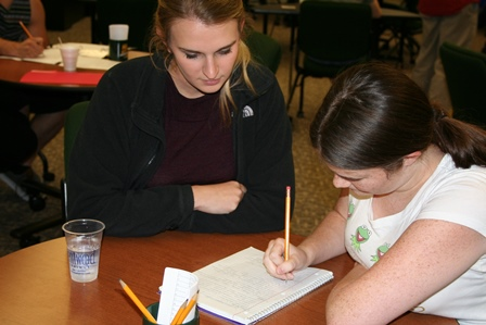 A writing consultants help students with course papers, other students study in the background